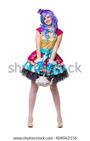 Happy woman wearing colorful dress and blue wig posing with teapot. Isolated on white