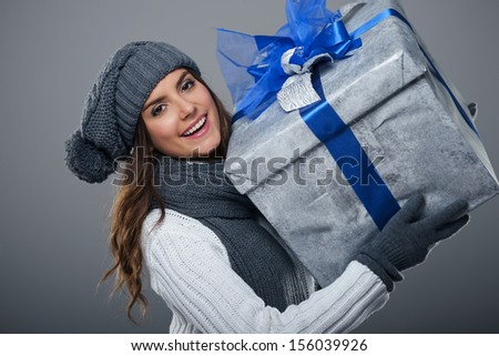 Happy woman wearing warm clothing holding big present  - stock photo