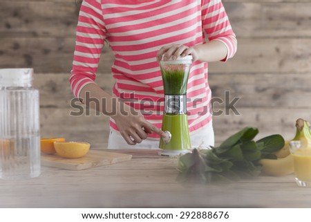 Happy woman with a blender  - stock photo