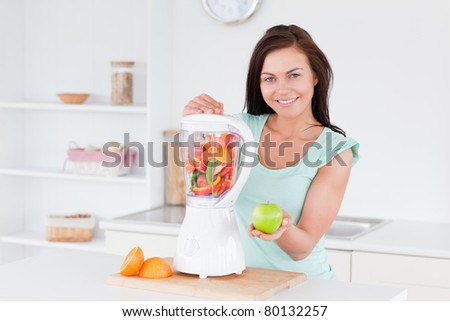 Happy woman with a blender and an apple - stock photo