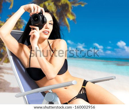 Happy woman with a digital camera taking photos on the beach - stock photo