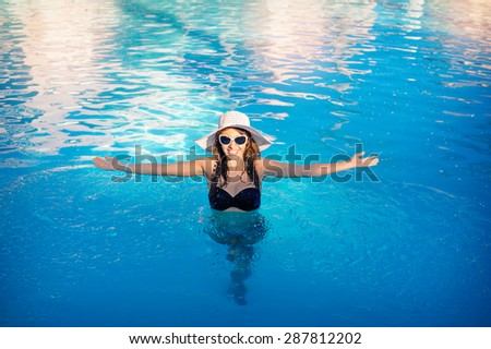 happy woman with a hat floating in a swimming pool.