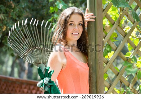 Happy woman with a rake gardening in the yard near a wooden fence - stock photo