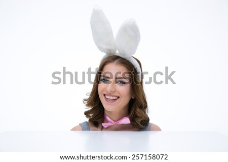 Happy woman with bunny ears sitting at the table and looking at camera - stock photo