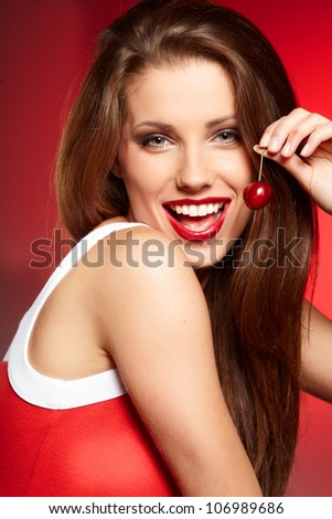 happy woman with cherries over red - stock photo