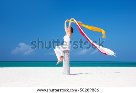 happy woman with colorful sarongs on the beach