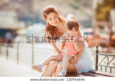 Happy woman with daughter resting at beach in summer outdoor - stock photo