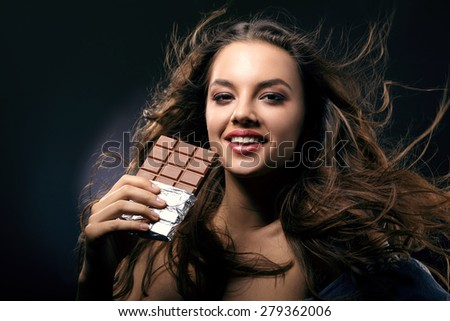 Happy woman with flowing hair and a chocolate bar in her hand close-up - stock photo
