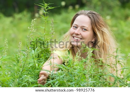 Happy woman with fresh hemp    at cannabis plant - stock photo
