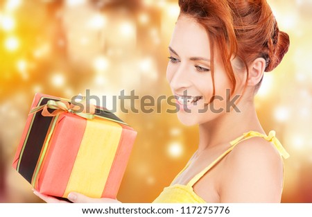 happy woman with gift box over christmas lights - stock photo