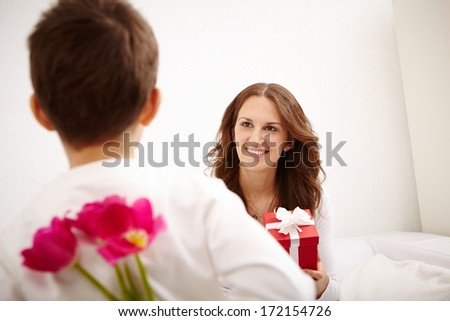 Happy woman with giftbox looking at her son and smiling - stock photo