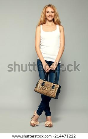 Happy woman with handbag in studio - stock photo