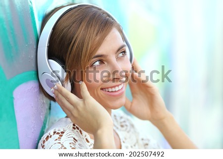 Happy woman with headphones listening to the music with a blurred graffiti wall in the background              - stock photo
