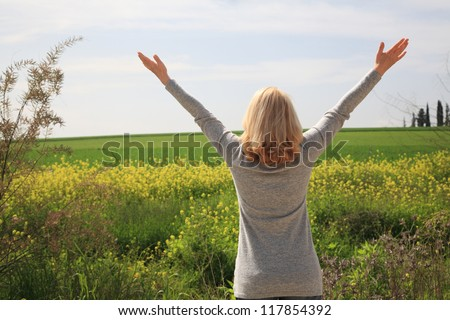 Happy woman with her arms wide spread is enjoying in the sunny day and surrounding nature. - stock photo