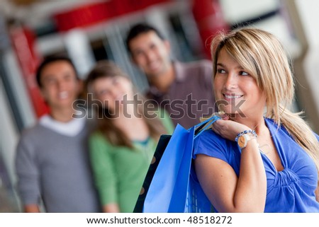 happy woman with her friends behind her smiling in a mall - stock photo