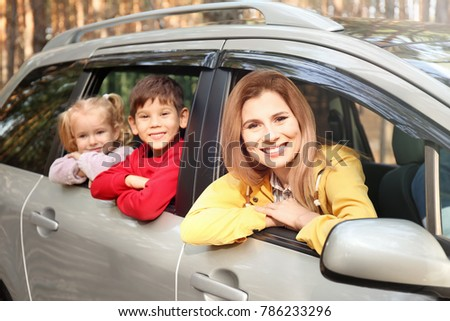 Happy woman with her little children in car on sunny day