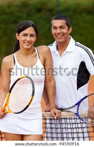 Happy woman with her tennis trainer at the court