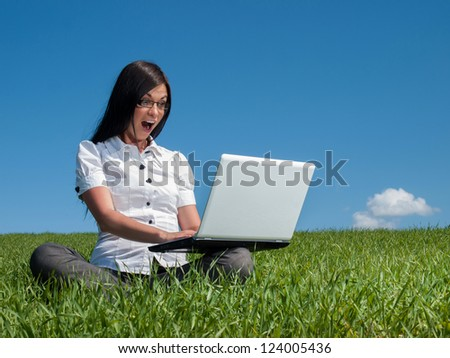 Happy woman with laptop on a meadow - stock photo