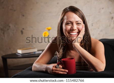 Happy woman with long hair sitting on sofa with mug - stock photo