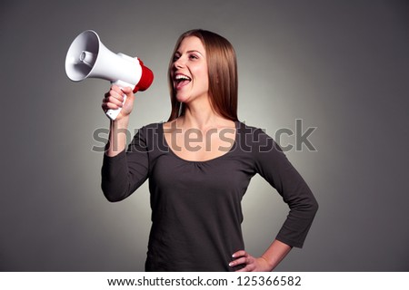 happy woman with loudspeaker over dark background