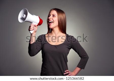 happy woman with loudspeaker over dark background - stock photo