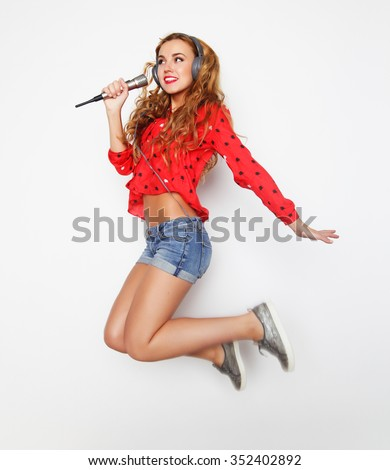 Happy woman with microphone jumping and singing - stock photo