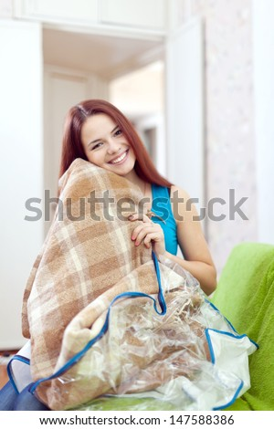 Happy woman with new plaid at home - stock photo