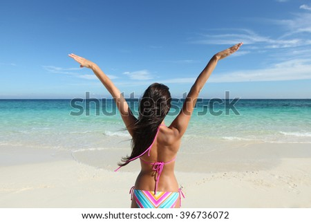 Happy woman with raised hands on beach  - stock photo