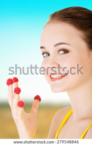 Happy woman with raspberries on fingers. - stock photo