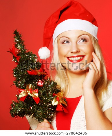 happy woman with Santa hat holding christmass tree - stock photo