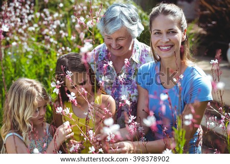 Happy woman with senior woman and girls in back yard during sunny day - stock photo
