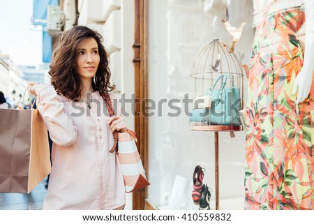 Happy woman with shopping bag looking at boutique showcase - stock photo
