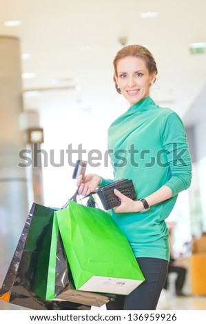 Happy woman with shopping bags and credit card in mall center. Sales.