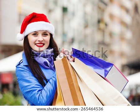 Happy woman with shopping bags at street during the Christmas sales
