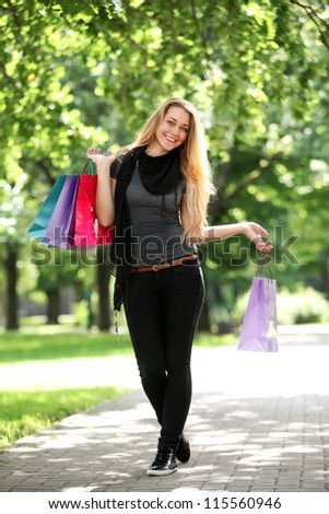 Happy woman with shopping bags in the park - stock photo