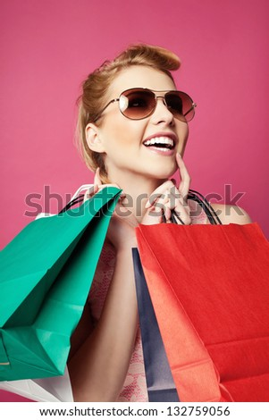 Happy woman with shopping bags screaming. Isolated on pink - stock photo