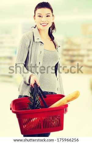 Happy woman with shopping basket  - stock photo