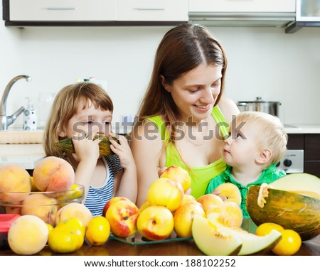 happy woman with two daughters eating melon and peaches