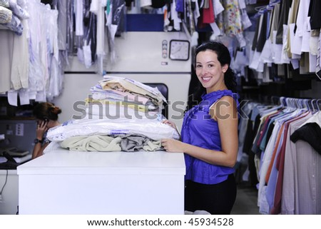 happy woman working at a dry cleaner store - stock photo