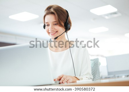 Happy woman working on laptop computer in call center