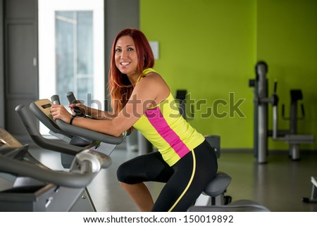 Happy woman working out on a gym cycle - stock photo
