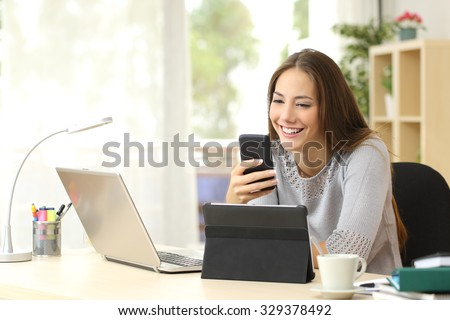 Happy woman working using multiple devices on a desk at home - stock photo