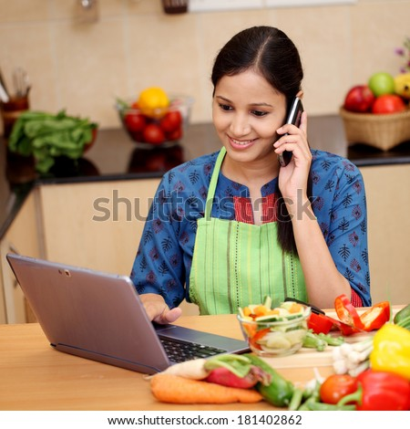 Happy woman working with tablet and talking on cellphone in kitchen - stock photo