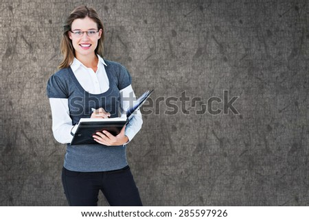 Happy woman writing in diary against grey background - stock photo