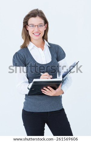 Happy woman writing in diary on white background - stock photo