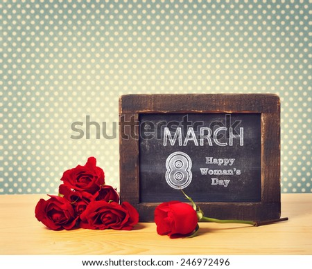 Happy Womans Day March 8th written on little chalkboard with roses - stock photo