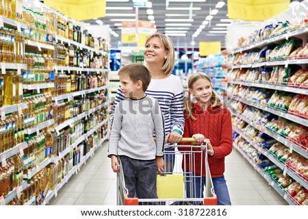 Happy women and children with cart shopping in supermarket