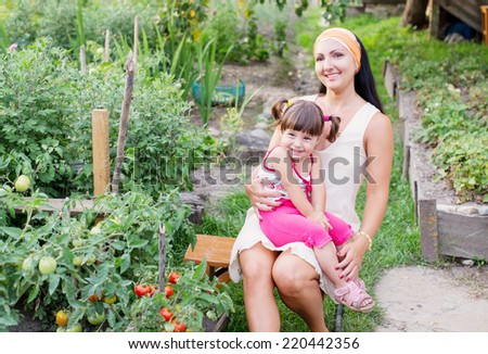 happy women and little child with tomatoes