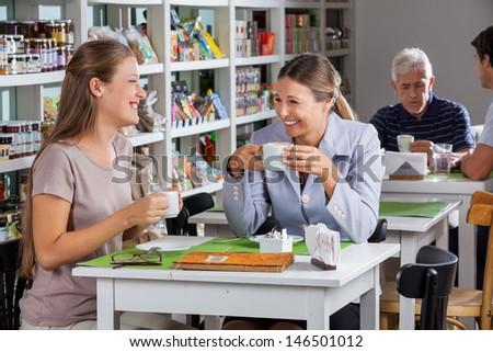 Happy women communicating while having coffee at supermarket - stock photo