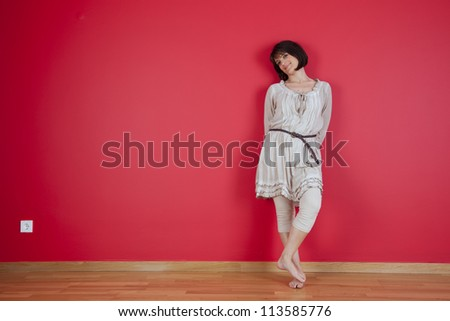 happy women dancing next to the red wall of his new house - stock photo